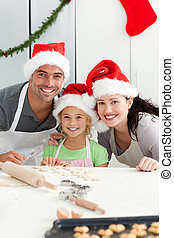 Cheerful family kneading biscuits for Christmas standing in...
