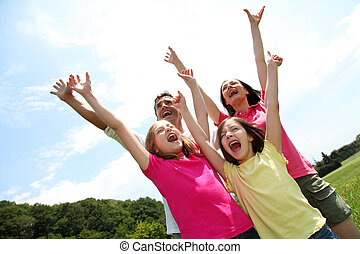 Cheerful family lifting arms up in the air