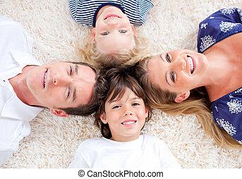 Cheerful family lying on the floor