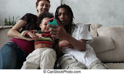 Cheerful family making selfie with smart phone