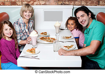 Cheerful family of four enjoying dinner