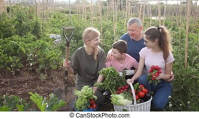 Portrait of happy friendly family with two teen children discussing good crop of vegetables in garden on sunny summer day