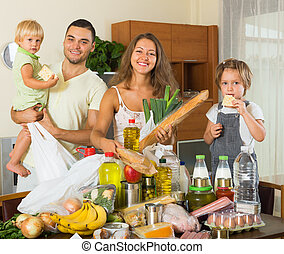Cheerful family of four with bags of food