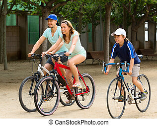 cheerful family of three cycling on city road