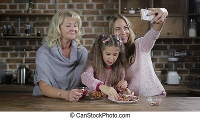 Cheerful family posing for selfie at kitchen table -...