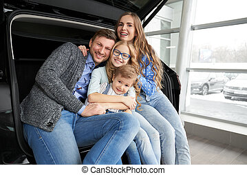 Cheerful family posing in car trunk of automobile.