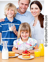 Cheerful family preparing breakfast in the kitchen