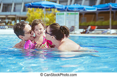 Cheerful family relaxing in the swimming pool