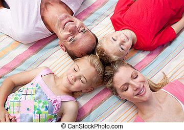 Cheerful family sleeping lying on the grass