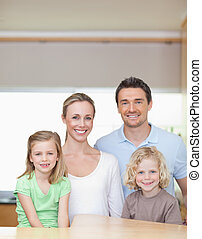 Cheerful family standing in the kitchen together