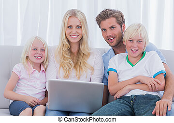 Cheerful family using a laptop