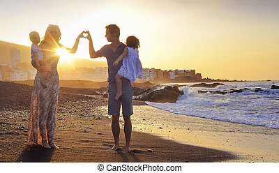 Cheerful family walking on the tropical beach