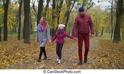 Cheerful family with girl walking in autumn park - Cheerful...