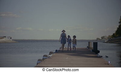 Cheerful family with kids walking along wooden jetty -...