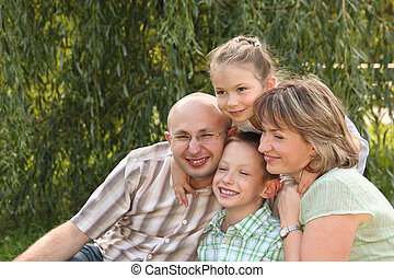 cheerful family with two children in early fall park. father, mother, little boy and girl is sitting near osier