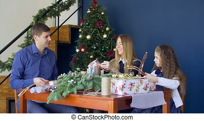 Cheerful famiy wrapping Christmas gifts at home - Positive...
