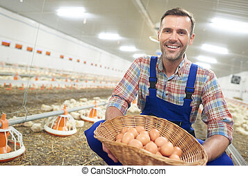 Cheerful farmer with basket full of eggs