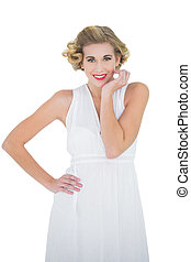 Cheerful fashion blonde model posing with a hand on the hip