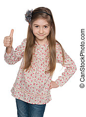 Cheerful fashion young girl holds her thumbs up