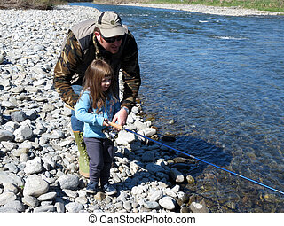 Cheerful father and daughter fishing together on the river