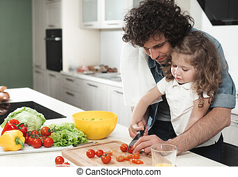 Cheerful father and daughter making salad in kitchen