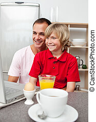 Cheerful father and his son having breakfast