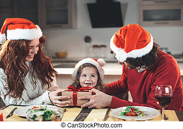 Cheerful father and mother giving present to their daughter