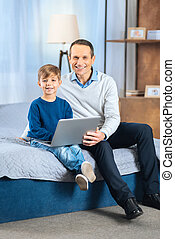Cheerful father and son posing with laptop on the bed