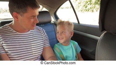 Cheerful father and son traveling by car