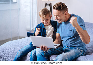 Cheerful father and son watching football online