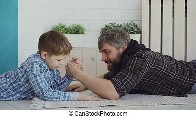 Cheerful father is teaching his little son arm wrestling, showing him hand position and pretenting to lose, boy is interested and concentrated on new activity.