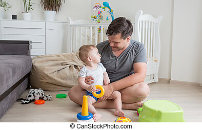 Cheerful father playing with his baby boy on floor at living room
