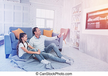 Cheerful father smiling while watching TV with his daughter