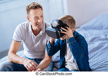 Cheerful father watching his son test VR headset