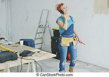 Cheerful female carpenter talking on smartphone