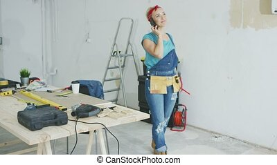 Cheerful female carpenter talking on smartphone - Happy...