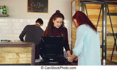 Cheerful female cashier is selling takeaway coffee to young...