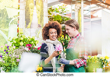 Cheerful female customer buying flowers at the advice of a helpful vendor