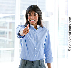 Cheerful female executive with a thumb up standing