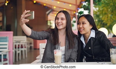 Cheerful female friends are making online video call with smartphone looking at screen and talking sitting in street cafe together. Communication and technology concept.