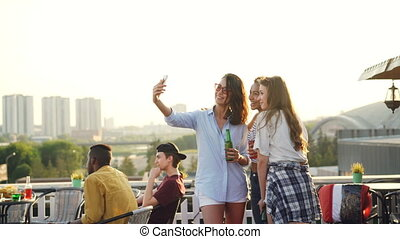 Cheerful female friends are taking selfie with smartphone and laughing standing on rooftop with drinks in bottles enjoying party. Technology, beverage and youth concept.