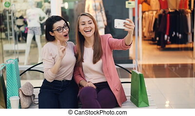 Cheerful female friends are taking selfie with smartphone sitting on bench in shopping mall and posing with glasses making funny faces. Photo, shops and friendship concept.