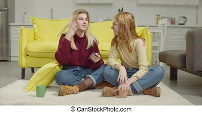 Cheerful female friends sharing smart phone at home
