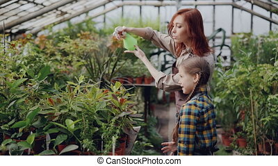 Cheerful female gardener is sprinkling water on plants and having fun with her adorable little daughter. Growing flowers, people and family concept.
