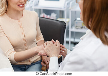 Cheerful female general practitioner talking with lady