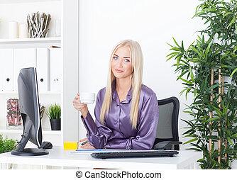 Cheerful female having a coffee break in the office