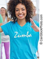 Cheerful female instructor doing pilates exercise