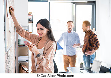 Cheerful female manager standing in office