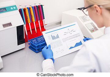Cheerful female researcher is working in laboratory