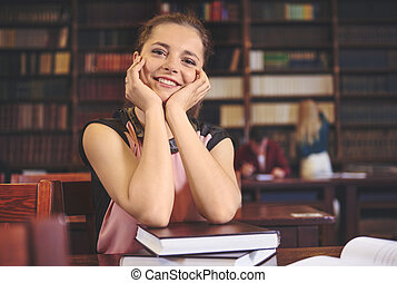 Cheerful female student at library